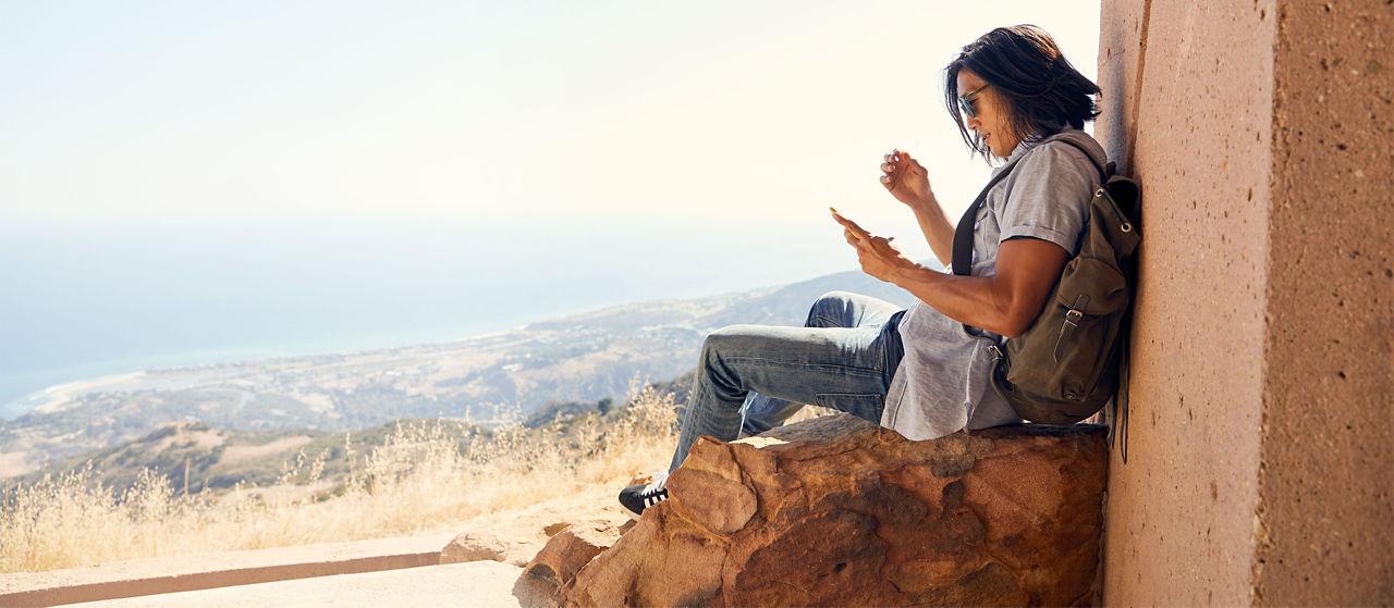 Mira las montañas y la costa mientras usa el smartphone