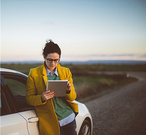 Woman leaning on car while using tablet