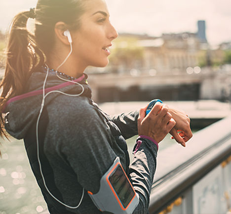 Woman resting from an outdoor jog, using her watch
