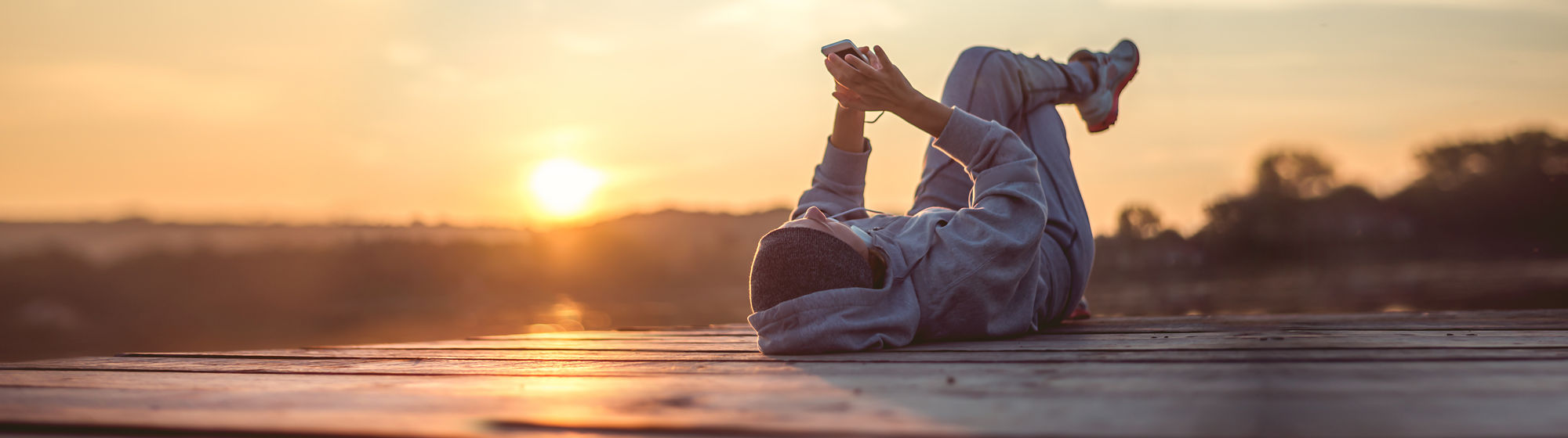 Guy using his smartphone in the sunset