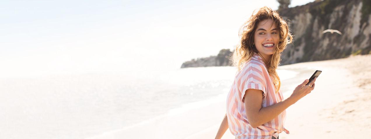 Mujer mirando hacia atrás mientras camina por la playa